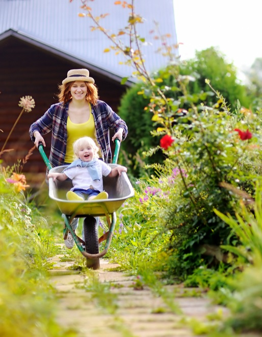 mother pushing child in wheelbarrow through garden