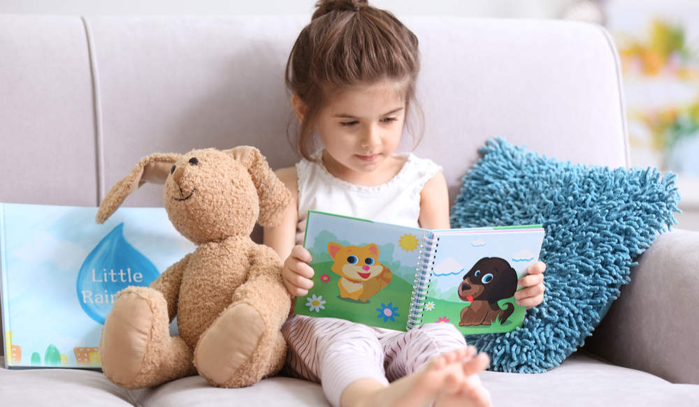 little girl reading a book with a stuffed animal